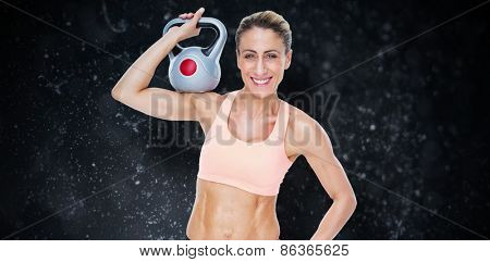 Female blonde crossfitter holding kettlebell smiling at camera against black background