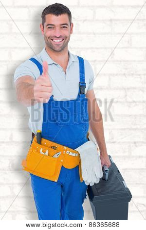 Happy repairman with toolbox gesturing thumbs up against white wall