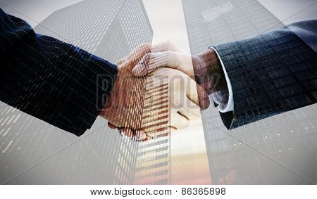 Business people shaking hands against low angle view of skyscrapers