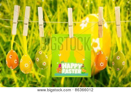 happy easter graphic against orange easter egg in the grass