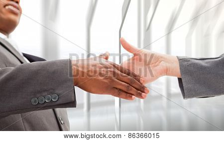 Businessman going shaking a hand against room with large window looking on city