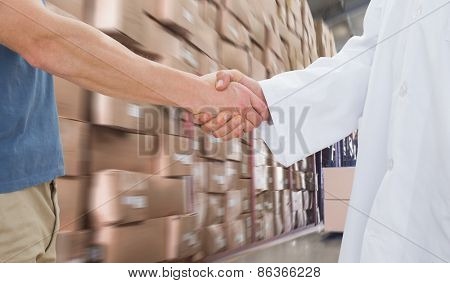 Mid section of a doctor and patient shaking hands against forklift machine in warehouse