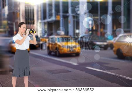 Serious elegant businesswoman looking through binoculars against blurry new york street