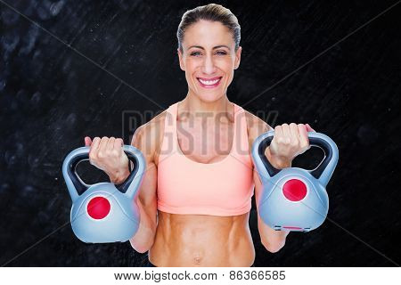 Smiling female crossfitter lifting kettlebells against black background