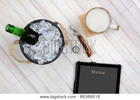 Overhead shot of an ice bucket with an opened beer bottle, a mug of beer and tablet computer for electronic ordering on a rustic white wood table. Horizontal format with copy space.