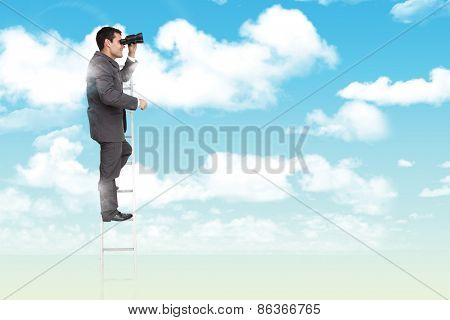 Businessman standing on ladder against blue sky