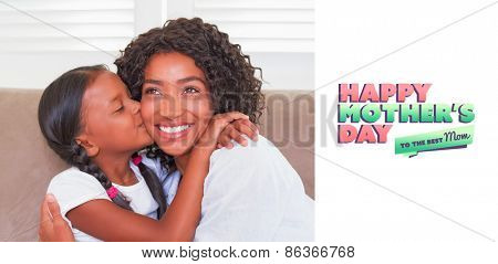 mothers day greeting against pretty mother sitting on the couch with her daughter kissing her cheek