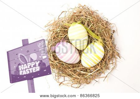 Easter egg hunt sign against three striped easter eggs in straw