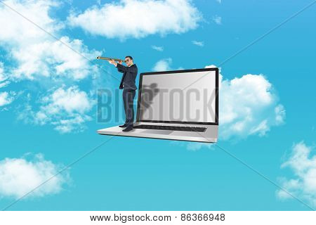 Businessman looking through telescope against blue sky