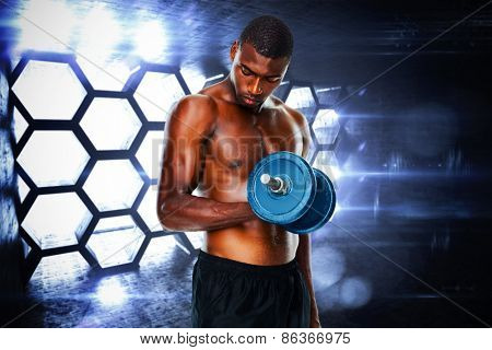 Determined fit shirtless young man lifting dumbbell against hexagon room