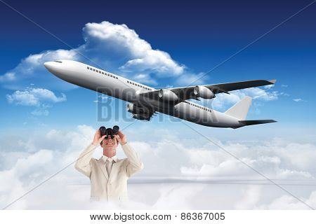 Confident businessman with binoculars against bright blue sky with clouds