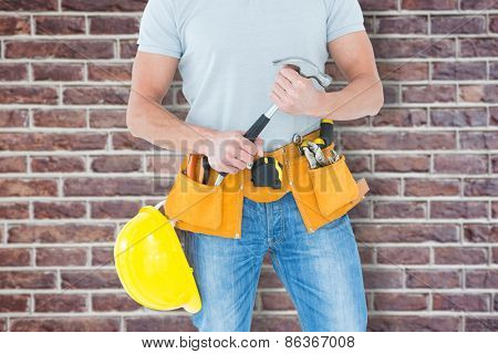 Worker holding hammer over white background against red brick wall