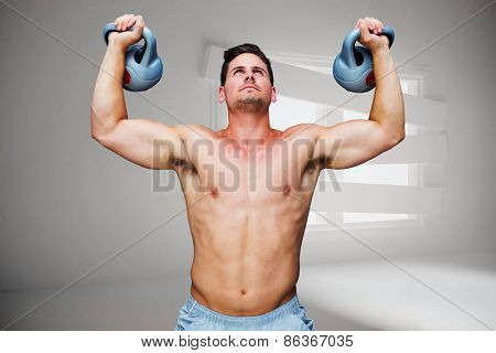 Bodybuilder holding kettlebells against digitally generated room with bordered up window