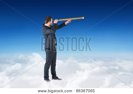 Businessman looking through telescope against blue sky over clouds