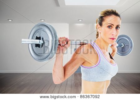 Strong female crossfitter lifting barbell behind head looking at camera against digitally generated room with stairs