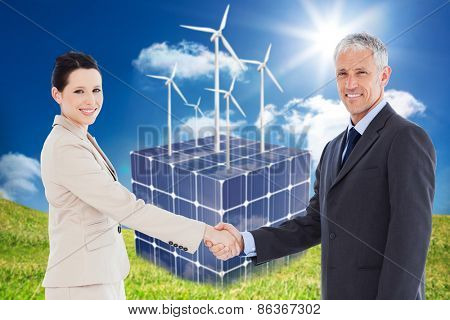 Smiling business people shaking hands while looking at the camera against turbines on a cube made of solar panels