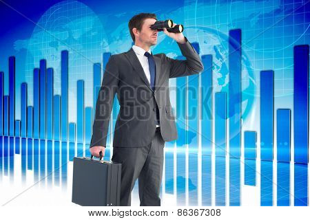 Businessman looking through binoculars against global business graphic in blue