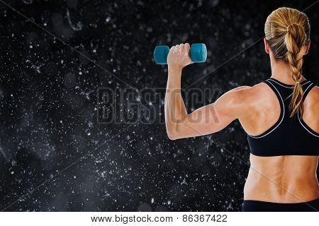 Female bodybuilder holding a blue dumbbell against black background