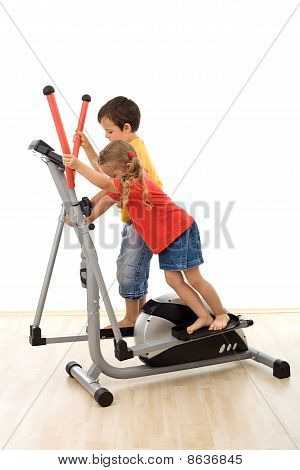 Teamwork - Kids Playing On Elliptical Trainer
