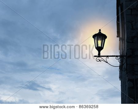 Old fashioned street light on sky background