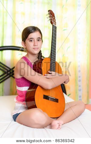 Hispanic teenage girl playing guitar in her bedroom
