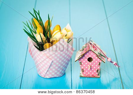 Yellow Spring Crocus And Birdhouse On Blue Wooden Background
