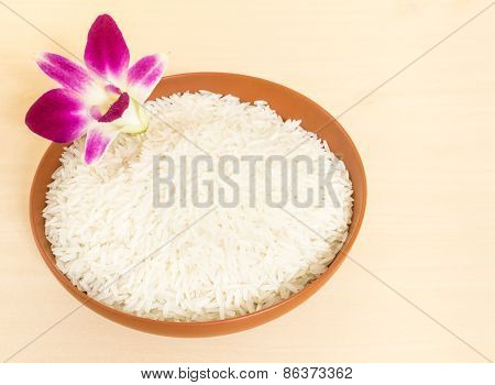 Thai Fragrant Jasmine Rice In A Brown Ceramic Bowl Garnish With Orchid Flower On Wood Table