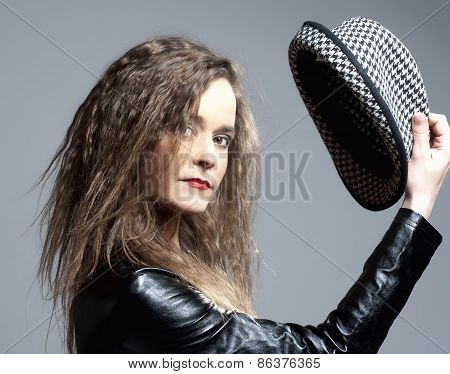 Beautiful Woman With Brown Curly Hair Holding A Hat