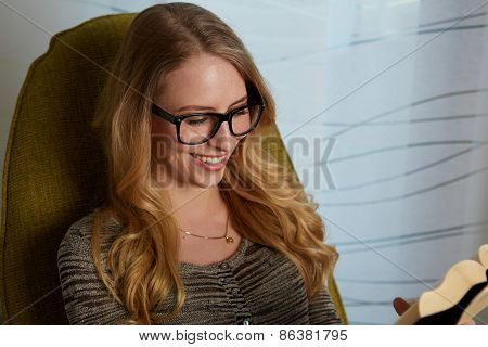 Young woman wearing warm sweater relaxing on cozy chair