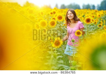 Happy woman in sunflower field.