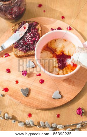 Cup of tea with a pouring milk, fresh baked homemade healthy bread with blackcurrant jam - homemade