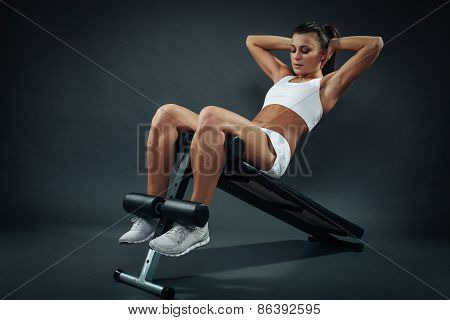 Attractive Young Woman Doing Sit Ups On Incline Bench