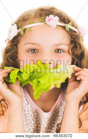 Beautiful healthy little curly girl enjoying eating a lettuce leaf