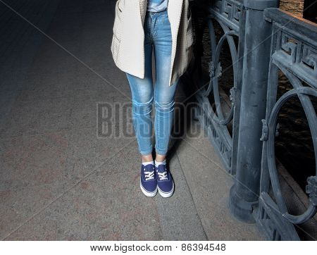 Part of the hipster girl standing in blue jeans outdoors in the evening near metal fence