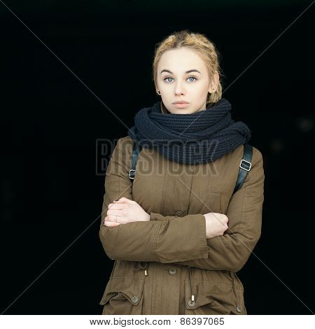 Outdoors portrait of young beautiful blonde hipster woman in olive parka with a dreadlocks bun