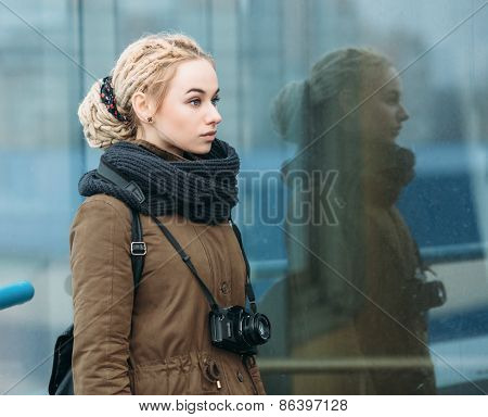 Outdoors portrait of young beautiful blonde hipster woman photographer with a film camera
