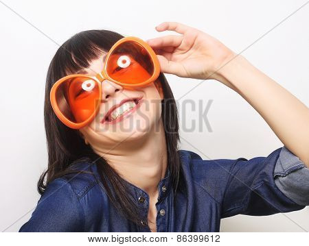 young happy woman with big orange sunglasses, ready for party