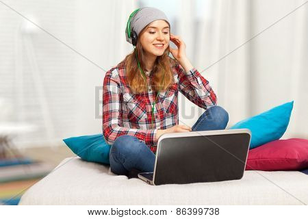 Teenage girl listening to music from her laptop