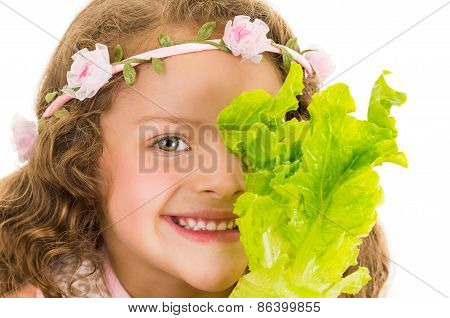 Beautiful healthy little curly girl holding lettuce in front of her eye