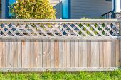 stock photo of wooden fence  - wooden fence with green lawn and houses - JPG