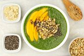 picture of granite  - Green smoothie bowl with mangoes granola almonds and chia seeds overhead view on white granite - JPG