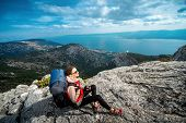 stock photo of sleeping bag  - Young woman mountain climber with backpack and sleeping back resting on the rocky mountain