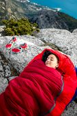picture of sleeping bag  - Young woman sleeping in red sleeping bag on the rocky mountain - JPG