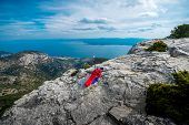 picture of sleeping bag  - Young woman lying in red sleeping bag on the rocky mountain