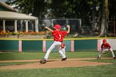 image of throw up  - Young pitcher on the mound in a youth baseball game - JPG