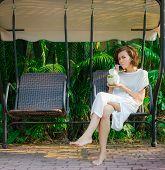 image of swingset  - Woman drinks fresh coconut on the swinset - JPG