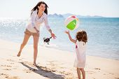 pic of babysitter  - Happy young mother and her daughter playing with a beach ball on a sunny day - JPG