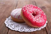 picture of doilies  - Delicious donuts with icing on lace doily on wooden background - JPG