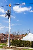 foto of utility pole  - Electric worker is climbing up on a pole - JPG