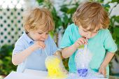 foto of experiments  - Two little boys making experiment with colorful soap bubbles and water outdoors - JPG